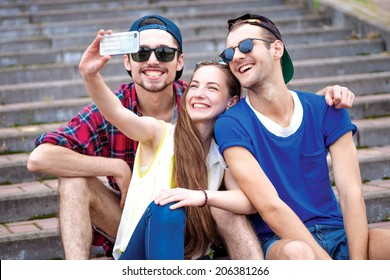 Photographing themselves by mobile phone on vacation. Young friends have fun together on the street and smile at each other. Funny guys make Selfie