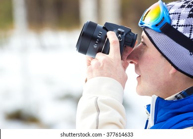 Photographing winter nature ; A young man in ski gear with a camera photographed winter landscapes under the snow