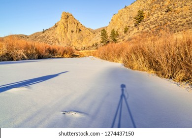 photographing winter sunset over Cache la Poudre River (North Fork) at Eagle Nest Open Space in northern Colorado with a shadow of camera nad photographer