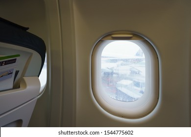 Photography of airplane window view to airport. Flying without incidents, fear of flying and turbulence.  Beautiful landscape looking through the aircraft cabin window.