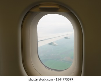 Photography of airplane window view to sky and earth. Beautiful landscape looking through the aircraft cabin window. Flying without incidents, fear of flying and turbulence.