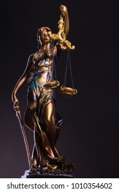 Photography of bronze themis sculpture, femida or justice goddess on dark background
