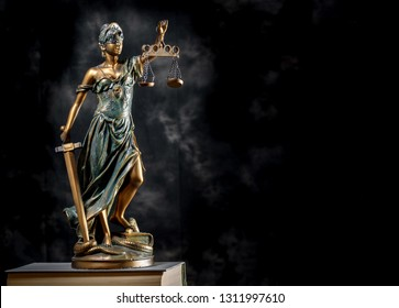 Photography of bronze themis sculpture, femida or justice goddess on dark background with books