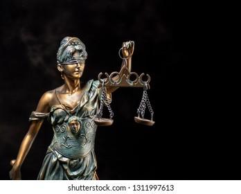 Photography of bronze themis sculpture, femida or justice goddess on dark background.