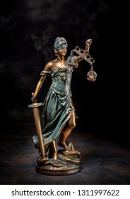 Photography of bronze themis sculpture, femida or justice goddess on dark background. With coins on scales