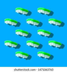 Photography collage of neon green color gummy milk teeth or jelly sweets on pastel blue background top view flat lay isometric pattern.Halloween holiday concept.surrealism,pop-art style.Square image