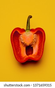 photography commercial Illustration of a red pepper showing inside and seeds on yellow background in studio.