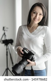 Photography is her hobby. Beautiful middle-aged woman standing in the studio and holding camera