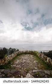 Photography made in a viewpoint of Lugo, Galicia. A viewpoint of stone and the city of Lugo is seen with a cloudy and gray sky.