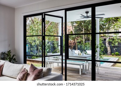 Photography of a modern patio with outdoor furniture in a landscaped poolside garden shot through the lounge room doors