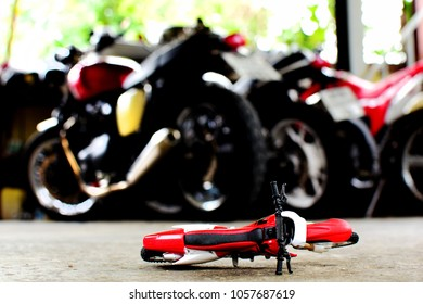 Photography of motorcycle toy on the floor and blurry motercycle background.