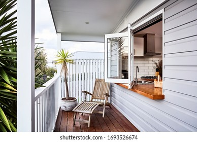 Photography of the outside porch of a small modern home studio/granny flat with bifold window and view of kitchen
