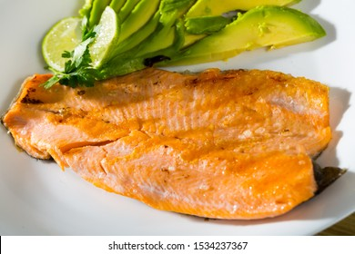 Photography of plate with fried trout fillet with avocado in restaurante.