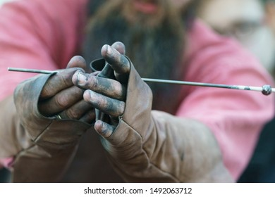 Photography of the process of making beads in workshop. Man glassblower make handmade products under burner. Ancient Slavic technique depends on bellows fanning. Professional russian worker. Flamework
