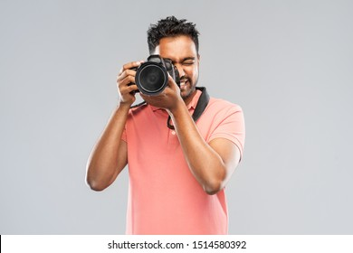 photography, profession and people and concept - happy indian man or photographer with digital camera over grey background