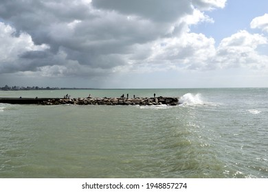 Photography of a rocky pier whit people fishing in it and a wave breaking against it whit a cloudy skyin the background