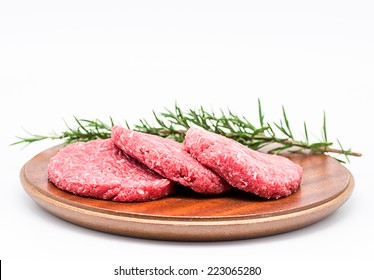 Photography Studio Three raw burgers with a sprig of rosemary on a white background