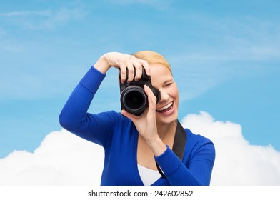 photography, technology, summer and people concept - smiling young woman taking picture with digital camera over blue sky and cloud background
