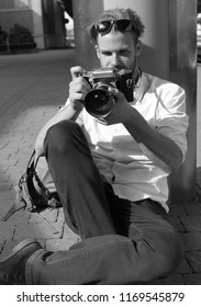 Photography and tourism concept. Tourist takes picture. Man with beard holds photocamera on urban background. Young traveller or photographer with concentrated face holds retro camera