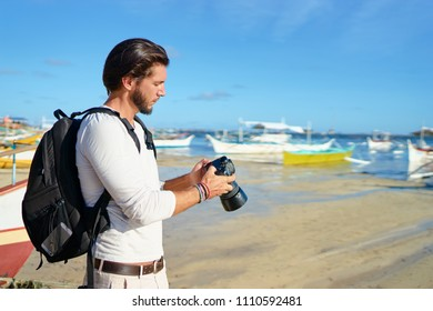 Photography and travel. Young man with rucksack taking photo with his camera enjoying beautiful tropical sea view on fishing beach.