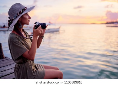 Photography and travel. Young woman in hat holding camera sitting on wooden fishing pier with beautiful tropical sea view.