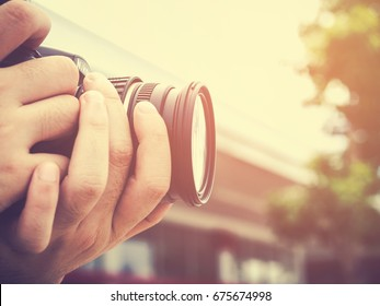 Photography or traveler Concept. The photographer hold DSRL camera in his hands with cityscape blur background and sunlight in summer time, selective focus. Photo of Vintage and filtered process.
