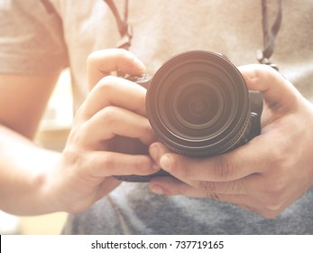 Photography or traveler Concept.The photographer hold black DSRL camera in his hands against building blur background and sunlight in summer season, selective focus. Vintage style.