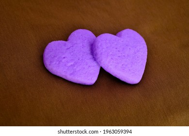Photography of two lilac heart shaped cookies on a brown cloth background