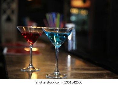 Photography of two martini glasses filled with cocktails standing on the bar counter. With blurred background.