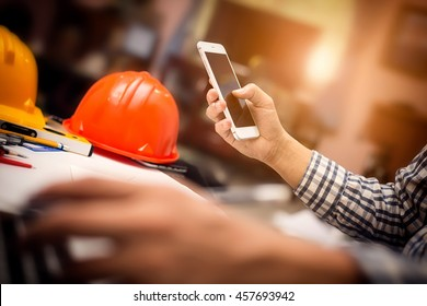 Photography of vintage picture style engineering working at construction office desk and holding mobile smartphone, architect engineer with new technology concept.