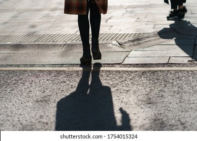 Photography of women feet and kids feet in spring sunlight. Shadowns at the road. Youth fashion style in Moscow. Back light.