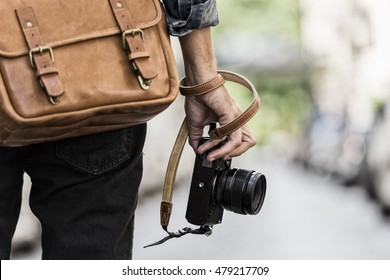 Photogrpher with leather bag in the city. Rear view