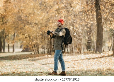 A photojournalist with a beard in an olive military cargo jacket, jeans, red hat with backpack holds his professional DSLR camera and checks the time on the wristwatch in the forest at the noon