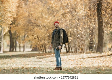 A photojournalist with a beard in an olive military cargo combo jacket, jeans, red hat with backpack and wristwatch holds his professional DSLR camera and waits in the forest at the noon