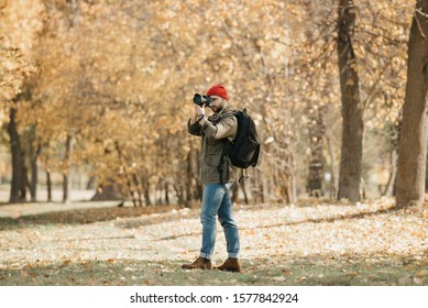 A photojournalist with a beard in an olive military cargo jacket, jeans, red hat with backpack and wristwatch takes photos with his professional DSLR camera in the forest at the noon