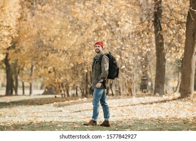 A photojournalist with a beard in an olive military cargo jacket, jeans, red hat with backpack and wristwatch holds his professional DSLR camera and waits in the forest at the noon