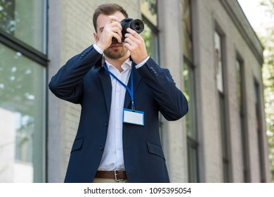 photojournalist in formal wear with press pass taking photo