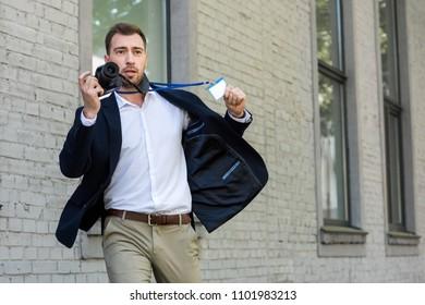 photojournalist running with digital photo camera and press pass