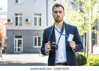 photojournalist working with digital photo camera and press pass