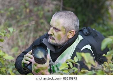 Photojournalist working in the jungle, camouflaged among the vegetation.