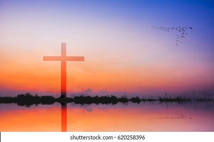 photomontage of cross against silhouette of mountain and lake view at sunsetet
