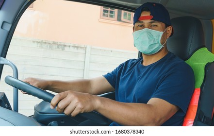 Photos of Asian truck drivers wearing masks to protect against dust and the spread of COVID 19 in front of the car. Safety ideas for a worker in the transportation business. And is a new normal life.
