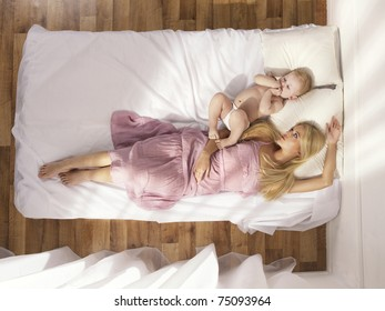 Photos of a beautiful young mother with a naked child in bed
