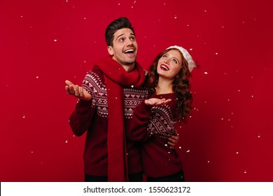 Photos of couple in burgundy knitted sweaters, catching snowflakes. Man and redhead girl hugging and posing on red background