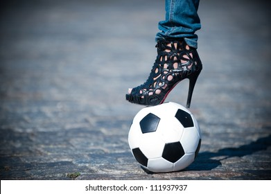 Photos of female feet in shoes with heels on the soccer ball