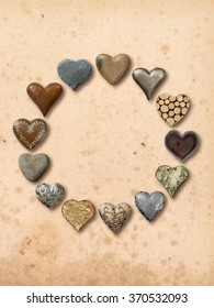 Photos of heart-shaped things made of stone, metal and wood, assembled into a circle over vintage paper background.