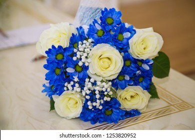Photos of the wedding bouquet in blue and white colors lying on the table. Bridal bouquet of roses and blue flowers.