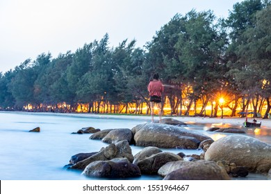 The photos were exposed for a long time, the sunset sky at Mae Ramphueng Beach, Rayong Province, Thailand. The woman wearing a red shirt stood on the rocks and was blurred with movement.