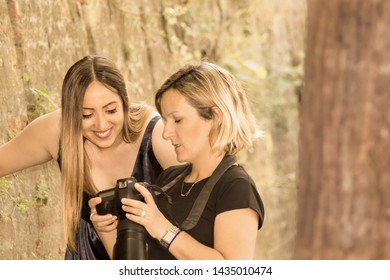 Photosession beautiful young blonde girl in a dress and blonde woman photographer looking at display of photocamera