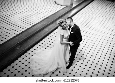 Photosession of stylish wedding couple on catholic church.